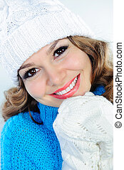 Smiling woman in knitted sweater, hat, and gloves - Winter...