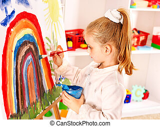 Child drawing on the easel. - Child drawing on the easel at...