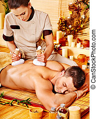 Man getting herbal ball massage treatments - Man getting...
