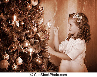 Child ignites candles on Christmas tree. - Little girl...