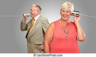 Senior Couple Having A Chat With A Tin On Gray Background