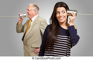 Senior Man Talking With Young Woman On Tin Can On Gray...