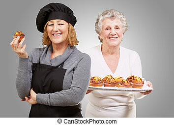 Female Chef Holding Muffins In Front Senior Woman