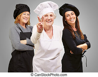 Three Happy Female Chef Gesturing On Gray Background