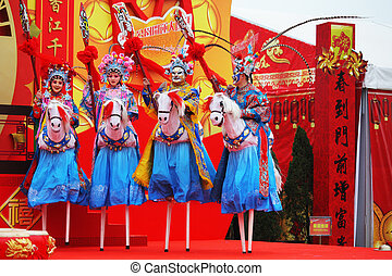 Beautiful dancers on stilts depict riders - Chinese New Year...