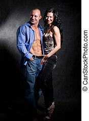 Muscular handsome sexy man with pretty woman on dark...