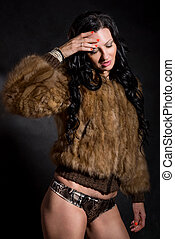 Beautiful sexy woman in fur coat on black
