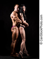 Muscular man and a woman posing in studio