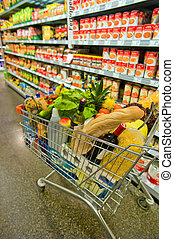 cart in a supermarket - a cart stands in a supermarket aisle...