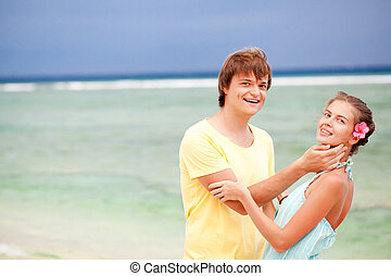 young happy couple having fun on tropical beach. honeymoon