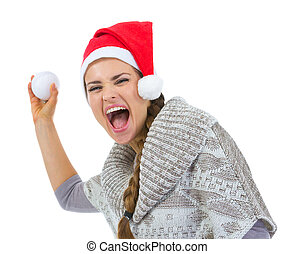 Cheerful woman in Santa hat throwing snowball