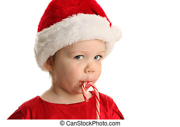 Baby eating a candy cane - Christmas Portrait of a beautiful...