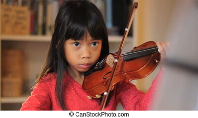 Girl Practices Her Violin - A pretty 6 year-old Asian girl...