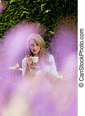 woman drinking coffee at breakfast in the garden