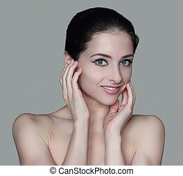 Beauty woman face with two hands at healthy skin isolated on grey background.