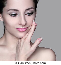 Beautiful woman with healthy skin touching hand face...