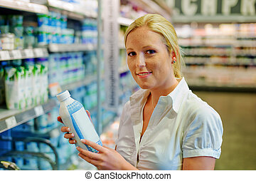 woman buying milk at the grocery store - a young woman buys...