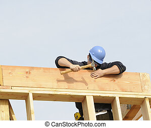 Carpenter hammering in nail on a commercial construction...