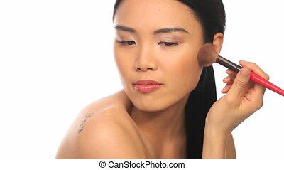 Blush application - Beautiful woman applying blush on her...