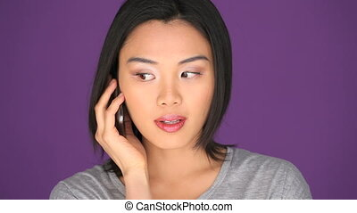 Woman shocked on cell phone - Portrait of an Asian Woman...