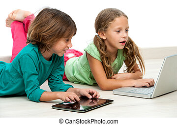 Two kids on floor with laptop and tablet. - Two kids laying...