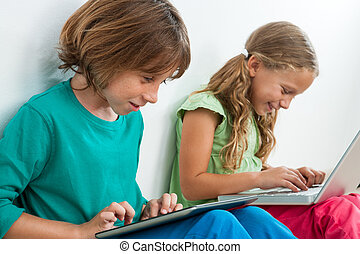 Two kids playing on tablet and laptop. - Two kids playing...