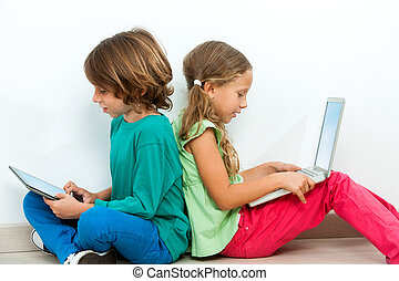 Two kids socializing with laptop and tablet - Two kids...
