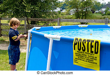 Posted No Trespassing - Boy fishing in a swimming pool with...