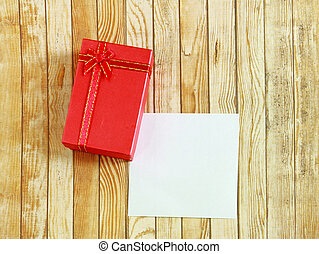 Red present box with blank note paper on wooden background