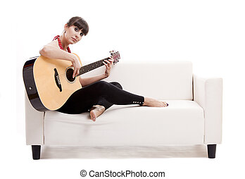 Playing guitar - Beautiful woman sitting on the sofa and...