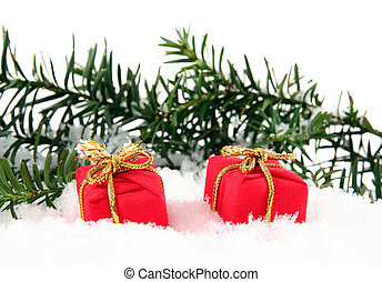 Two christmas gift box and branch on white snow