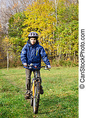 Boy riding bicycle in a park