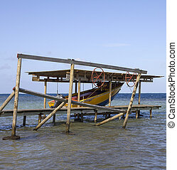 tropical boat house - old wooden boat house with a boat