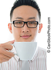 asian man having tea or coffee break, zoom on face