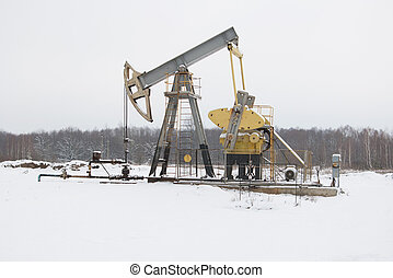 oil pump works on winter forest background