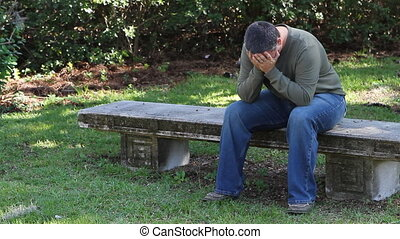 Depressed Man On Bench - Depressed adult male sits alone on...