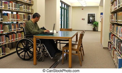 Wheelchair Laptop Library - Paraplegic adult male in a...