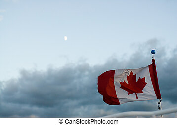 Patriotism - A Canada flag blowing high in the sky against a...