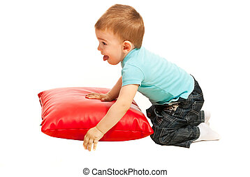 Toddler boy playing with pillow - Toddler boy laying with a...