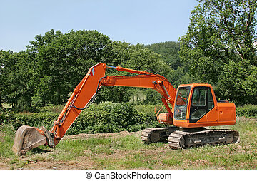 Earthmover - Orange digger standing idle in a field with...