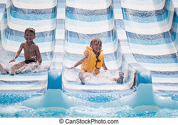 Children at aqua park - Happy children on water slide at...