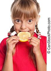 Little girl with lemon - Cute little girl eating fresh lemon...