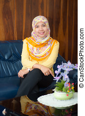 asian Muslim female with scarf relaxing on sofa