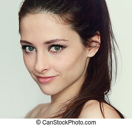 Beautiful young woman face with natural makeup looking...