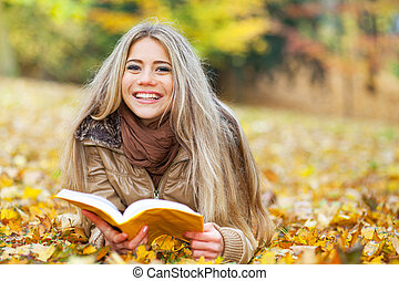 Young woman reading in a park in autumn - Pretty woman lying...