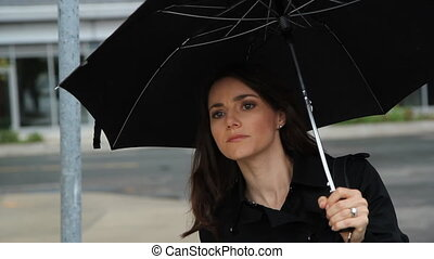 Waiting in the rain. Medium shot. - Woman on the street with...
