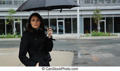 Waiting in the rain. Wide shot. - Woman on the street with...