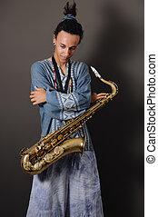Teen saxo player - Portrait of young musician standing with...