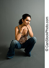 The kneel - a young attractive hispanic female crouches down...