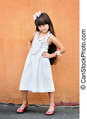 portrait of little girl outdoors in white sundress